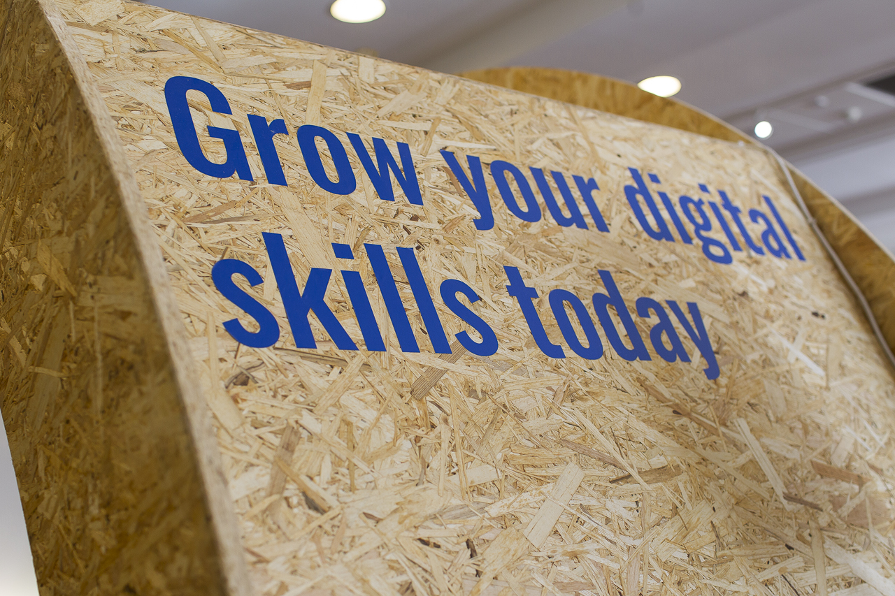 chipboard panel with the words, grow your digital skills today, painted upon it in blue writing