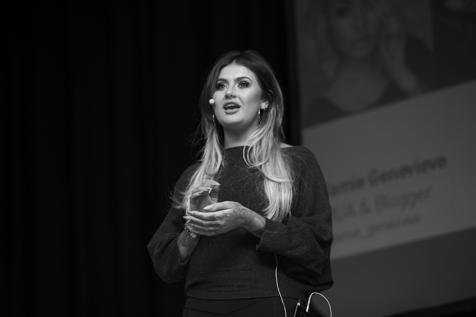 Make up artist and YouTuber, Jamie Genevieve, on stage doing a presentation