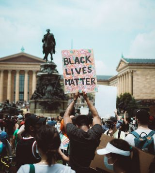"""A person of colour holding a placard saying """"Black Lives Matter""""."""