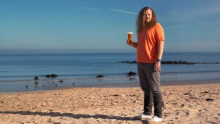 Tennent's Life is Bigger Than Beer Campaign - Dave on the beach holding a pint of Tennent's