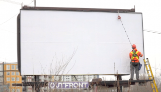 Photo of man putting up billboard of Blank Billboard Campaign in Nova Scotia