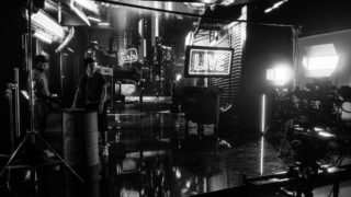 photo of two people on virtual production stage with lots of neon lights adjusting equipment